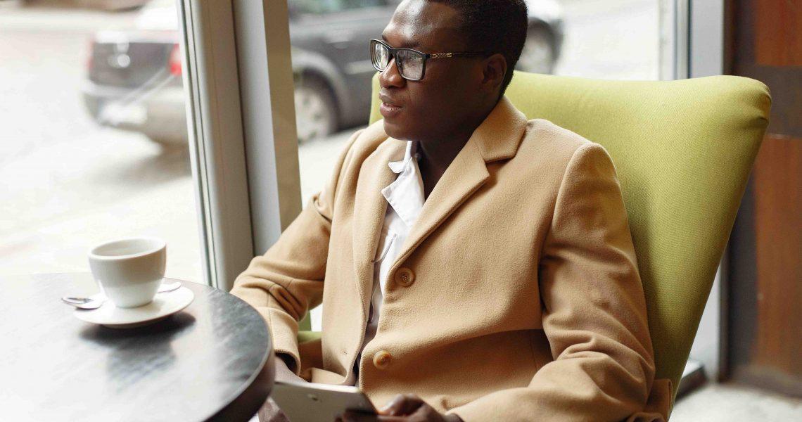 pensive-elegant-businessman-with-tablet-in-cafe-4173168